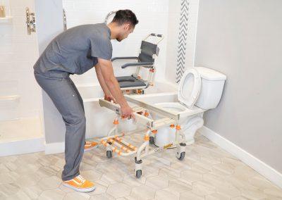TubBuddy SB2 chair over bathtub with caregiver removing bridge