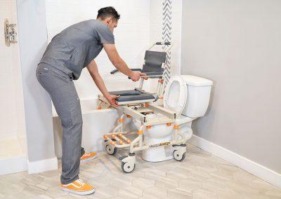TubBuddy SB2 chair transitioning to bathtub with caregiver