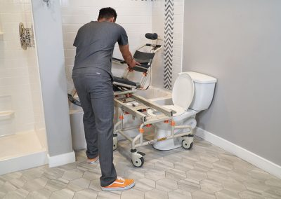 TubBuddy Tilt SB2T chair tilted in bathtub with caregiver