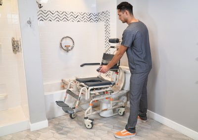 TubBuddy Tilt SB2T chair over toilet with caregiver